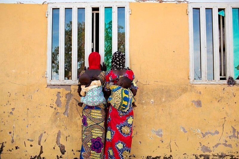 Women watch as people carry food supplies out of a storage building at the Fufore camp for internally displaced persons outsi