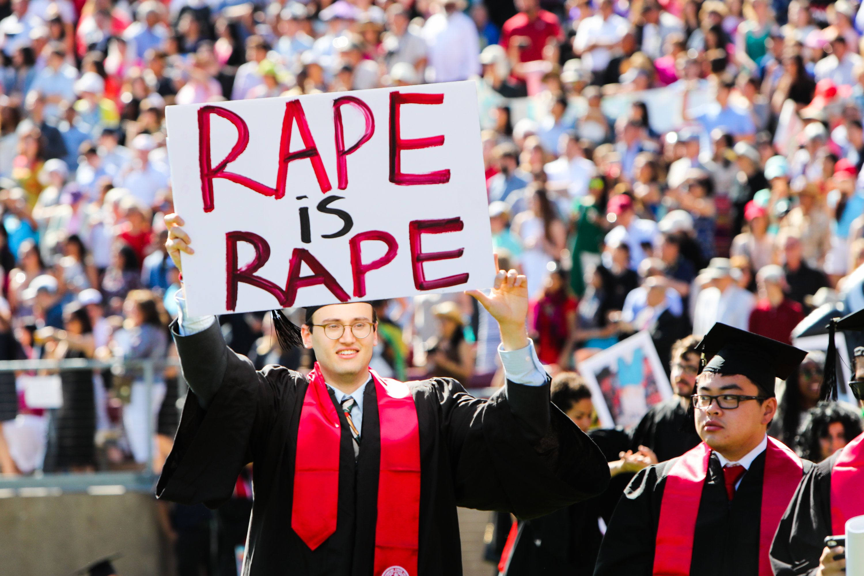 "A Stanford student holds a sign reading ""rape is rape"" during 2016 graduation ceremonies."