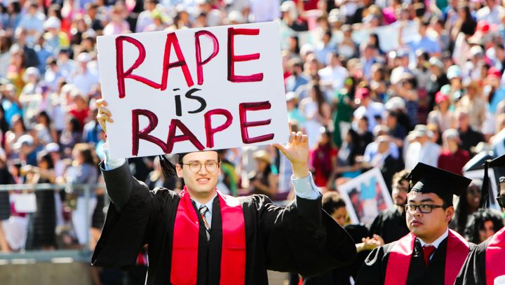 """A Stanford student holds a sign reading """"rape is rape"""" during 2016 graduation ceremonies."""