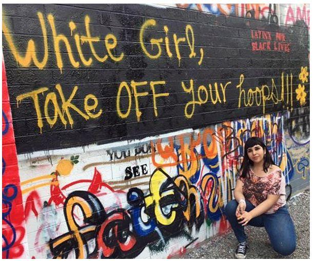 Alegria Martinez poses with graffiti.