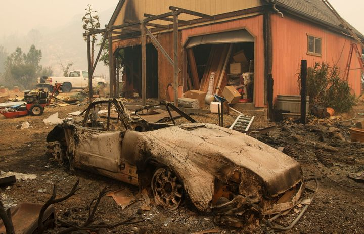 A burned out Porsche is seen near a partially burned home in the Santa Cruz Mountains near Loma Prieta, California on Septemb