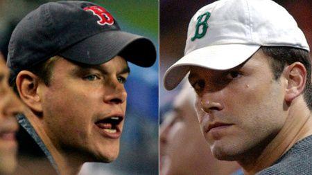 Matt Damon and Ben Affleck wearing Boston Red Sox hats.