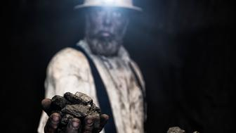 A dirty middle-aged Caucasian male coal miner covered in coal dust with a handful of coal nuggets, wearing a aluminum hardhat with a LED light attached looking at the camera while in a dark coal mine.