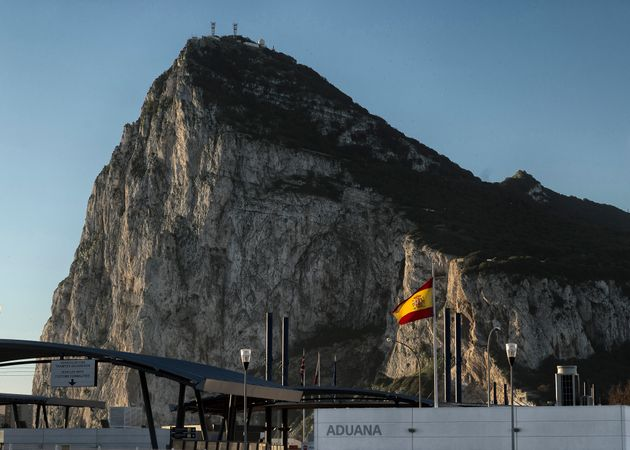 A Spanish flag flies on top of the customs house on the Spanish side of the border between Spain...