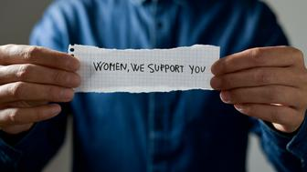 closeup of a young caucasian showing a piece of paper with the text women we support you written in it