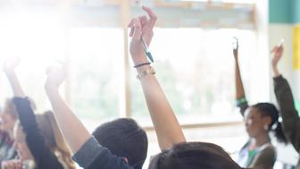 Teenage students with arms raised in classroom