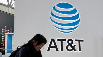A woman looks at her mobile next to AT&T logo during the Mobile World Congress in Barcelona, Spain February 25, 2016. REUTERS/Albert Gea/File Photo