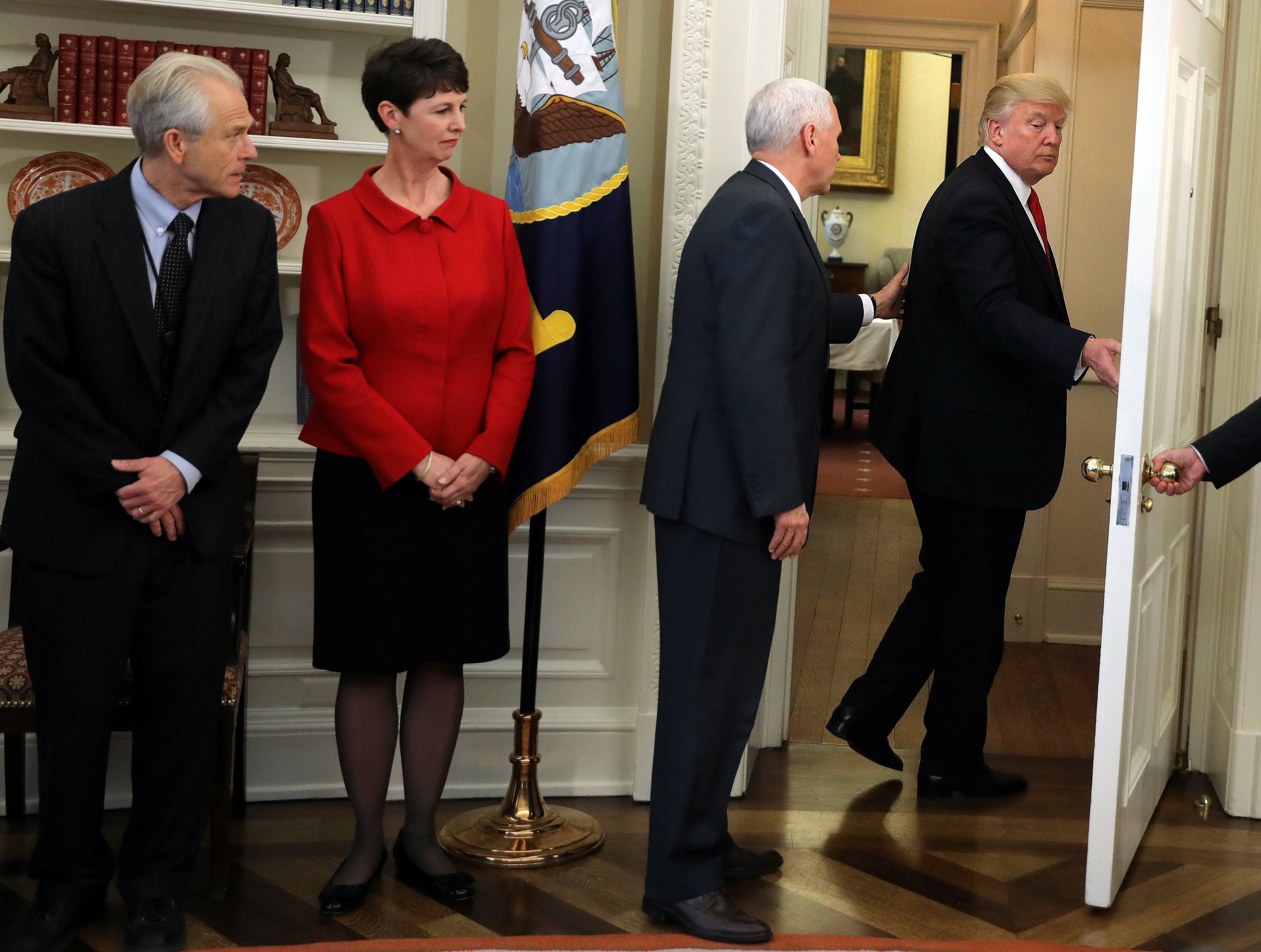 U.S. President Donald Trump leaves without signing executive orders on trade as Vice President Mike Pence (C) reacts during a signing ceremony at the Oval Office of the White House in Washington, U.S., March 31, 2017. REUTERS/Carlos Barria     TPX IMAGES OF THE DAY