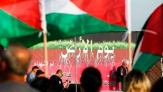 A picture taken on March 30, 2017 shows Palestinian flags flying before a dais showing a sign reading 'Land Day' during a gathering of Arab-Israelis marking the occasion in the northern Arab-Israeli village of Deir Hanna in the northern Galilee region. Land Day marks the killing of six Arab Israelis during 1976 demonstrations against Israeli confiscations of Arab land. / AFP PHOTO / HAZEM BADER        (Photo credit should read HAZEM BADER/AFP/Getty Images)