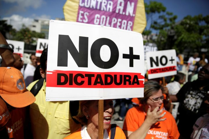 """An opposition supporter holds a placard that reads """"No more dictatorship"""" as she takes part in a rally against President Nico"""