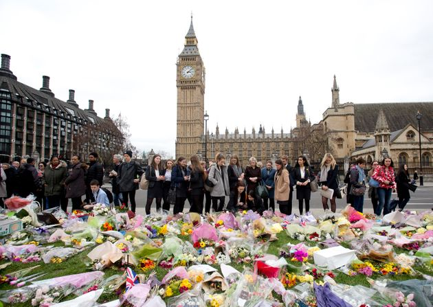 People pay their respect at the floral memorial in Parliament Square, Westminster,
