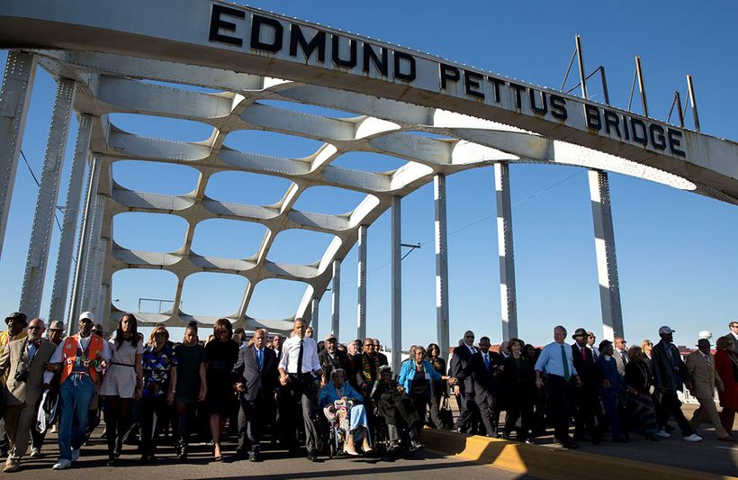 President Barack Obama, Rep. John Lewis, D-Georgia are joined by other dignitaries in marching across the Edmund Pettus Brid