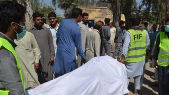 SARGODHA, PAKISTAN - APRIL 02: Pakistani emergency workers transport the body of a victim to hand over to their relatives at a hospital in the garrison city of Sargodha, in Punjab province, Pakistan on April 2, 2017. The custodian of a Pakistani religious shrine and two accomplices have been arrested for intoxicating and murdering 20 devotees with batons and knives early Sunday. (Photo by Sohail Ahmed/Anadolu Agency/Getty Images)