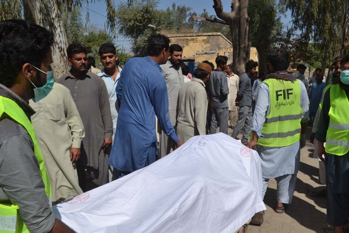 Pakistani emergency workers transport the body of a victim to hand over to their relatives at a hospital in the garrison city