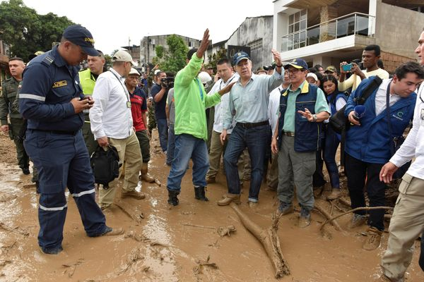 Santos, fourth from right, gestures while visiting a flooded area in Mocoa on April 1.