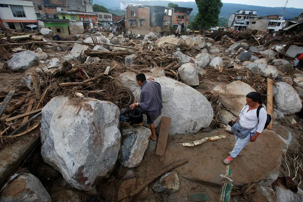People walk on a destroyed street in Mocoa on April 2.