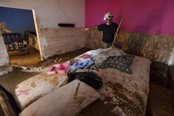 A fireman searches for victims inside a muddy house in Mocoa on April 2.