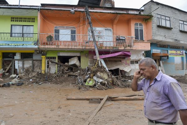 A man talks on his phone while walking down a damaged street in Mocoa on April 2.