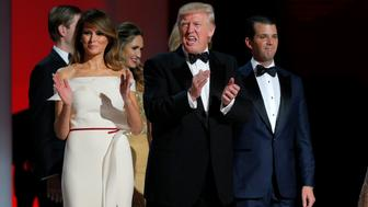 "U.S. President Donald Trump applauds while flanked by his wife Melania (L) and his son Donald Jr. (R) at his ""Liberty"" Inaugural Ball in Washington, U.S., January 20, 2017.   REUTERS/Brian Snyder"