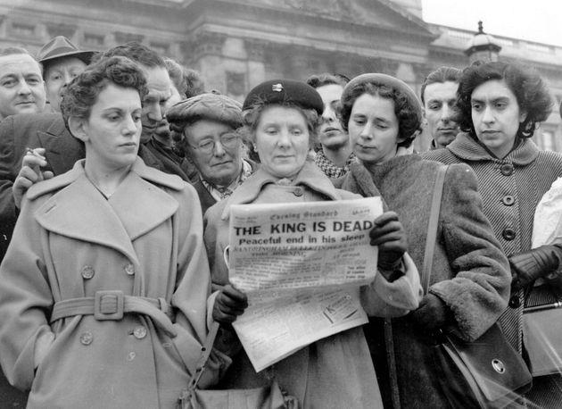 Una multitud se reúne ante Buckingham Palace para leer en los periódicos que el rey Jorge VI ha muerto,...
