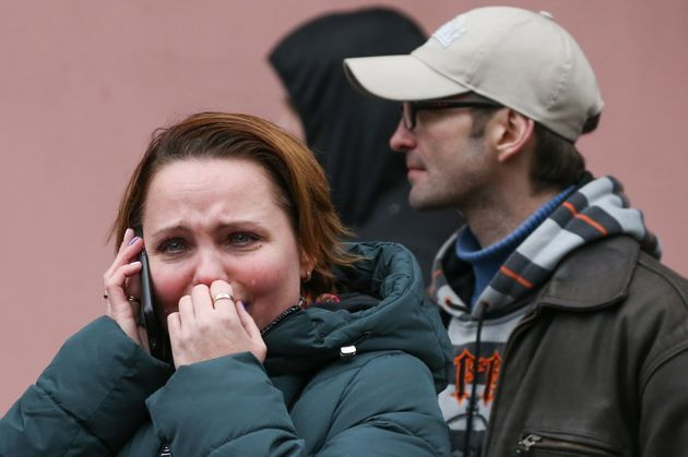 A woman weeps while talking on the mobile phone at the entrance to Tekhnologichesky Institut