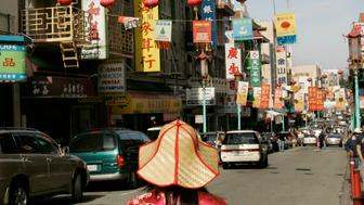 "A woman looks at Chinese New Year banners hanging along a street in the Chinatown neighborhood of San Francisco, California February 5, 2007. The Chinese New Year, the ""Year of the Pig"", begins on February 18.  REUTERS/Robert Galbraith  (UNITED STATES)"
