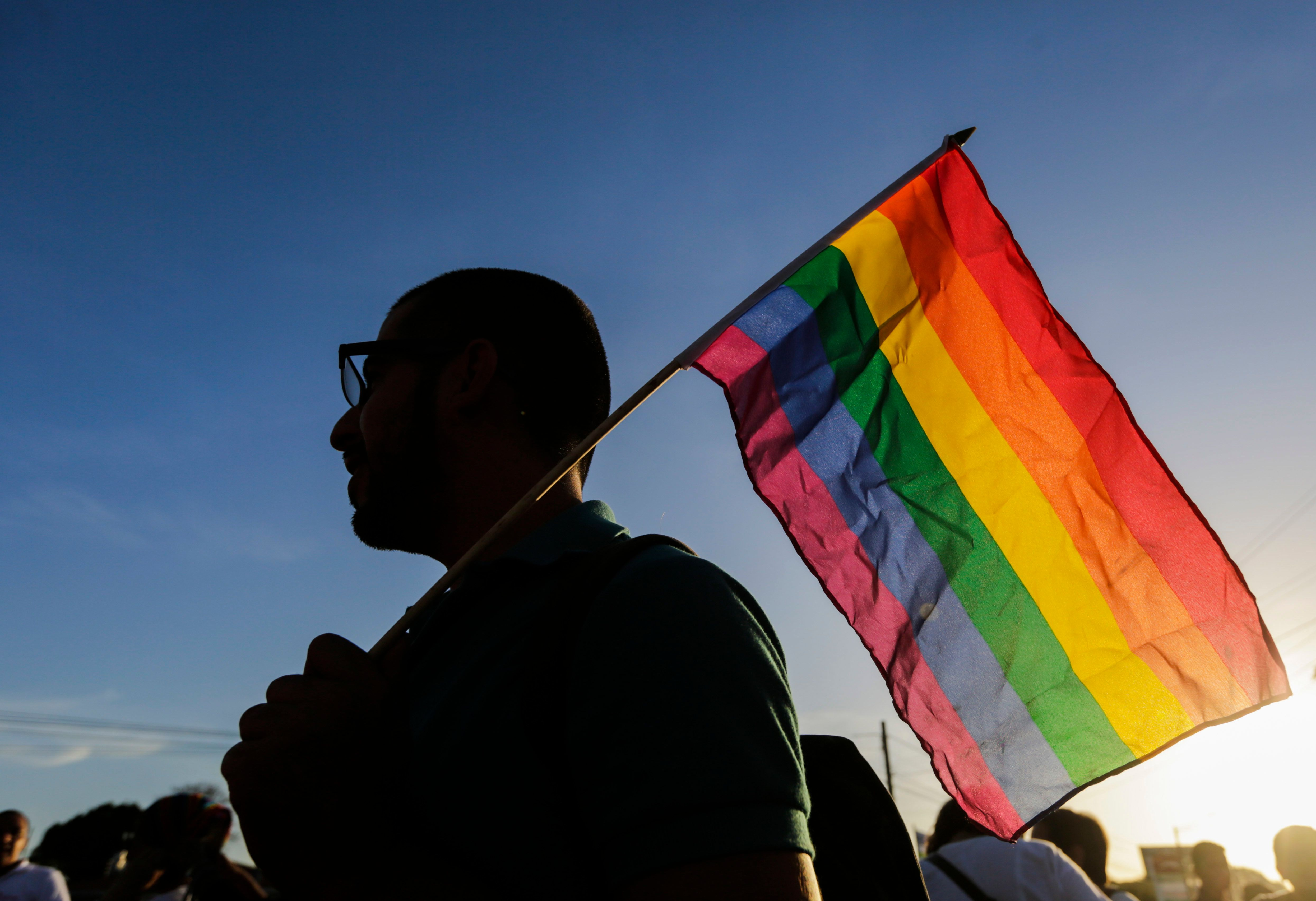 A Nicaraguan LGBT community member and supporter holds up a rainbow flag at the Metrocentro roundabout in Managua on June 14, 2016, in solidarity with the victims of the Orlando mass shooting.  Forty-nine people were killed and 53 others wounded when a heavily armed gunman opened fire and seized hostages at a popular gay nightclub in Orlando, Florida -- the worst terror attack on US soil since September 11, 2001. / AFP / INTI OCON        (Photo credit should read INTI OCON/AFP/Getty Images)