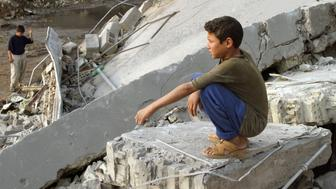 """Iraqi boy views the damage to a destroyed restaurant in Falluja, following an overnight air raid conducted by U.S. forces.  An Iraqi boy views the damage to a destroyed restaurant in Falluja, following an overnight air raid conducted by U.S. forces over the western city, October 12, 2004. American warplanes flattened Falluja's most popular restaurant overnight, killing two security guards, in what the military said was a """"precision strike"""" aimed at its top enemy in Iraq. REUTERS/Mohanned Faisal pictures of the month October 2004"""