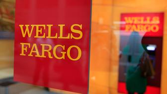 A Wells Fargo sign is seen outside a banking branch in New York July 13, 2012. Wells Fargo & Co reported a 17 percent increase in second-quarter profit Friday on strong mortgage banking income and improved credit quality. REUTERS/Shannon Stapleton (UNITED STATES - Tags: BUSINESS LOGO)