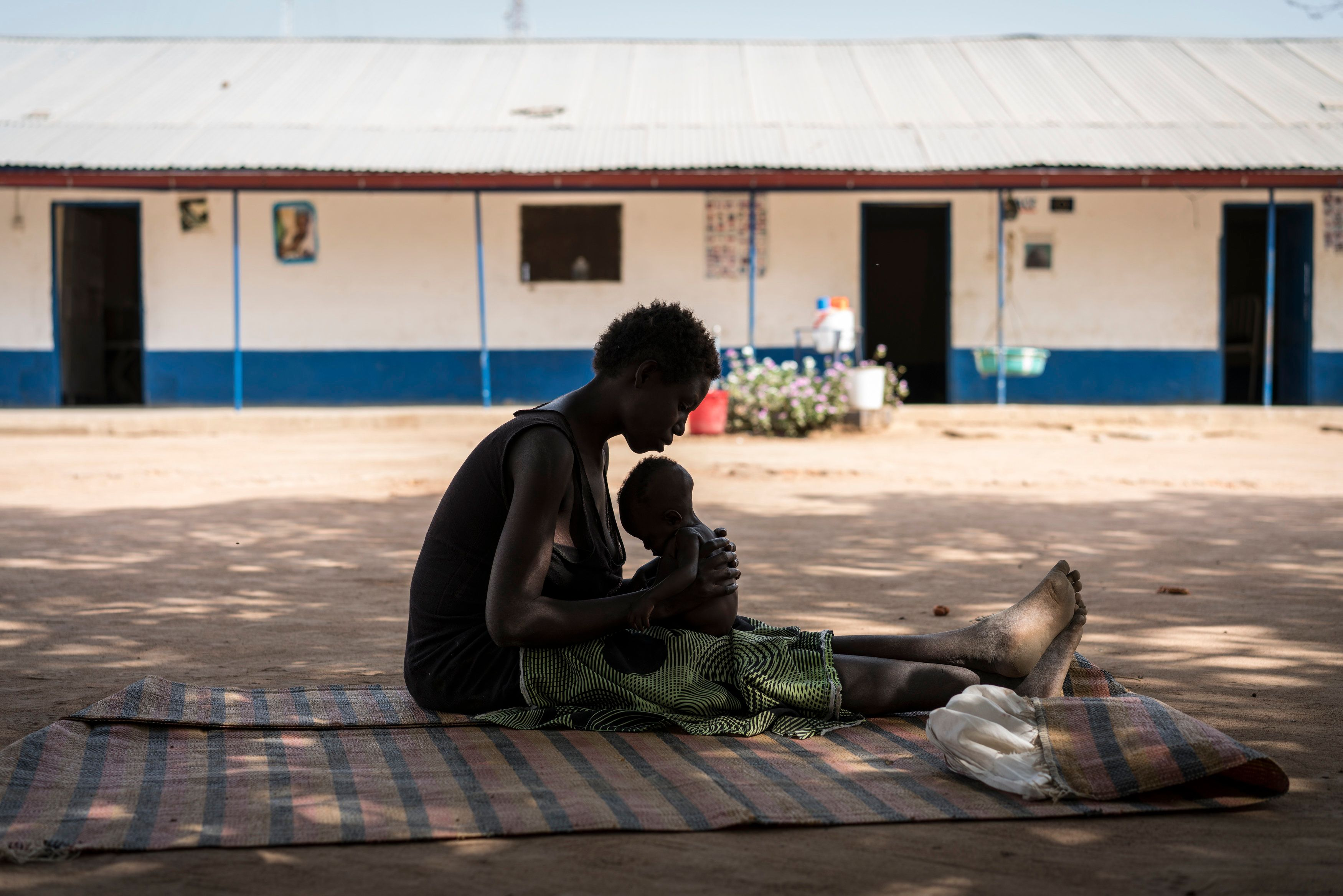 A young mother cradles her malnourished child outside a UNICEF-supported center in South Sudan on March 11.