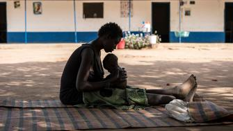 A young mother cradles her malnourished child outside a UNICEF-supported stabilization centre in Malualkon, Aweil, South Sudan, Saturday 11 March 2017.  Now entering its fourth year, the conflict in South Sudan has disrupted farmers' abilities to plant and harvest. That combined with the country's skyrocketing inflation and increasingly unpredictable rains has put an estimated one million people on the brink of starvation with many now being forced to forage for food to survive. Last month, famine was declared in parts of South Sudan. In Aweil State, children and their families are facing a hunger crisis at emergency and critical levels. Over 280,000 children are severely malnourished and without a coordinated effort to reach them, one in nine is likely to die. UNICEF and its partners are significantly scaling up the emergency response to avert a famine and save lives. Reaching mothers and babies at the community level, UNICEF is providing life-saving treatment to address severe malnutrition; provision of clean water, sanitation and hygiene; malaria testing and treatment; and critical information to mothers on preventative nutritional practices including the promotion of breast-feeding. Altogether, UNICEF aims to reach over 200,000 children who are severely malnourished.