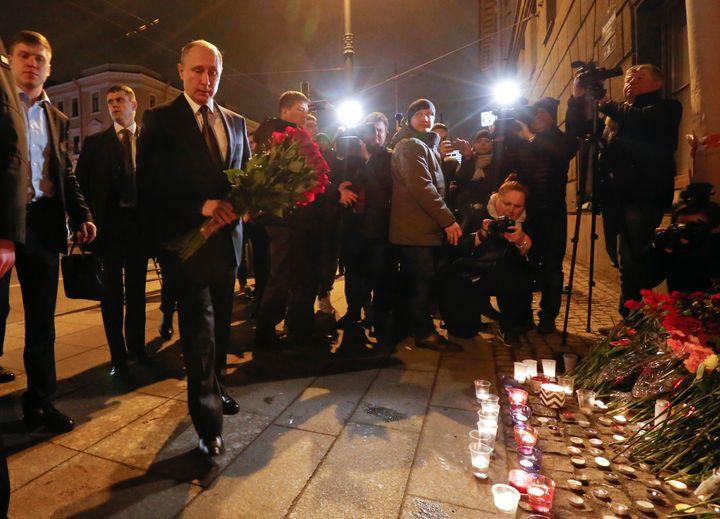 Russian president Vladimir Putin puts flowers down outside Tekhnologicheskiy Institut metro station in St Petersburg, Russia.