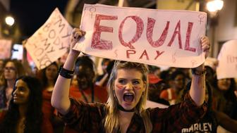 MIAMI, FL - MARCH 08:  Clarissa Horsfall holds a sign reading, 'Equal Pay,' as she joins with others during 'A Day Without A Woman' demonstration on March 8, 2017 in Miami, United States. The demonstrators were calling for woman to have equity, justice and human rights for women and all gender-oppressed people.  (Photo by Joe Raedle/Getty Images)