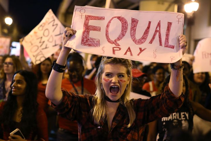 "Clarissa Horsfall holds a sign for equal pay during a ""Day Without A Woman"" demonstration on March 8, 2017 in Miami."
