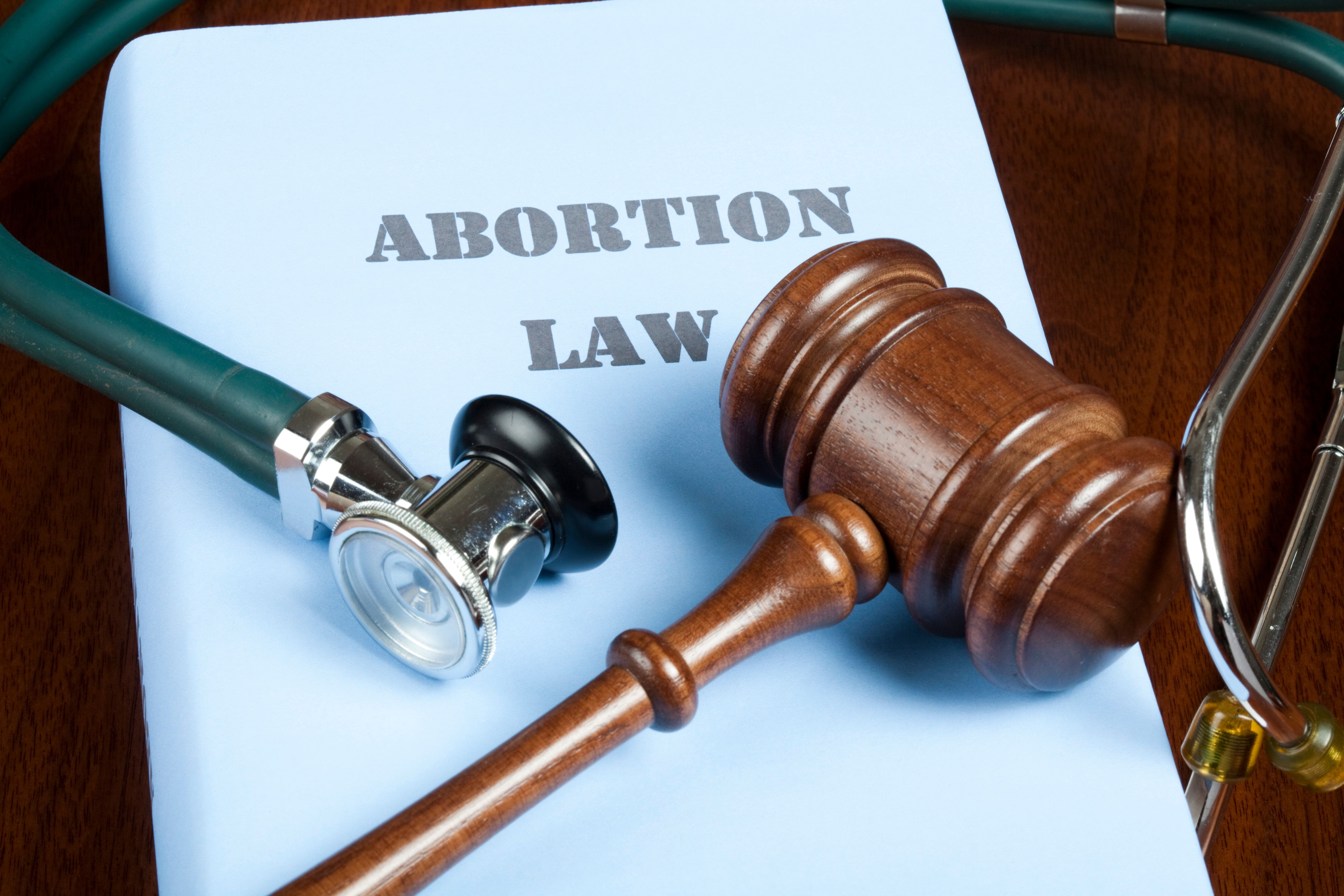 Gavel and stethoscope on Abortion law handbook.