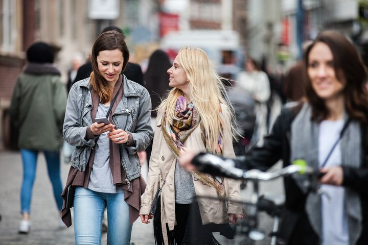 Three friends meetup in Copenhagen downtown during a beautiful spring day. LeoPatrizi via Getty Images