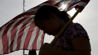 KILLEEN, TX - APRIL 04:  Jenna Ryan,11, holds a flag as she participates in a flag walk in memory of those killed and injured by Iraq war veteran, Ivan Lopez, on April 4, 2014 in Killeen, Texas. Lopez killed three and wounded 16 before taking his own life on the Fort Hood Army base.  (Photo by Joe Raedle/Getty Images)