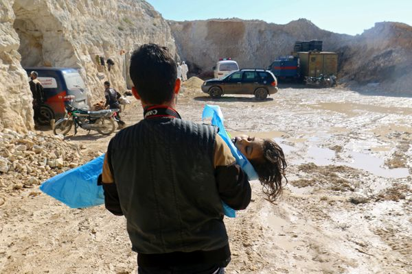 A man carries the body of a dead child, after what rescue workers described as a suspected gas attack in the town of Khan She