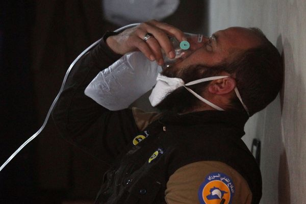 A civil defence member breathes through an oxygen mask, after what rescue workers described as a suspected gas attack in the