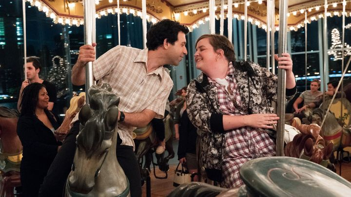 Ray and Abigail lean in for a kiss on the carousel on Brooklyn Bridge Park.