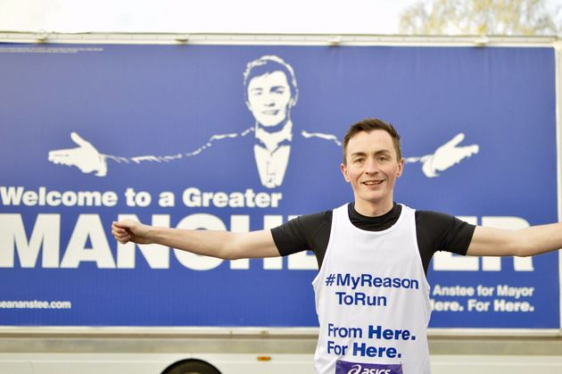 Sean Anstee poses in front of a billboard at the Greater Manchester