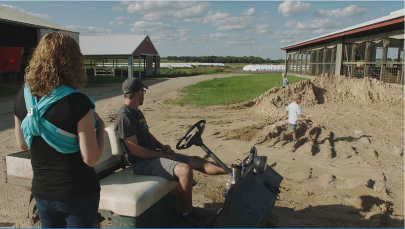 Allison and Dan Lauderdale watch two of their sons playing in the sand pile on the farm