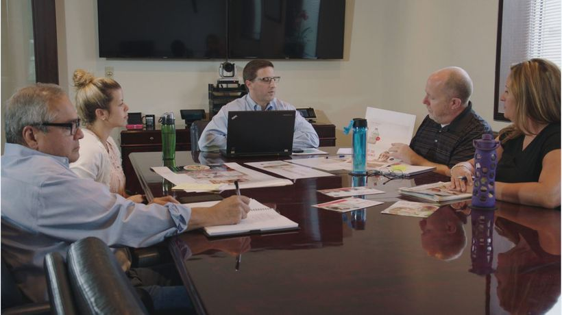 Bruce Bedford, VP of Analytics (center), leads a meeting with the Oberweis marketing team