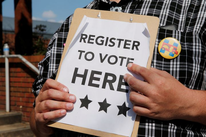 A man holds voter registration forms outside a campaign rally with 2016 Democratic presidential candidate Hillary Clinton in