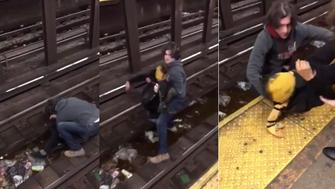 A 29-year-old man is being hailed a hero after rescuing a fallen man from an oncoming subway trains tracks