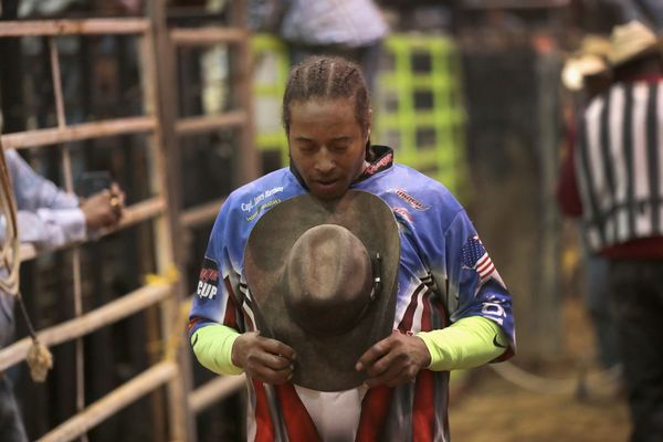 Bullfighter Teaspoon Mitchell says a prayer before the start of the bull riding competition.