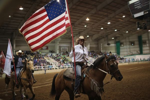 Carolyn Carter carries the American flag as contestants parade through the arena.