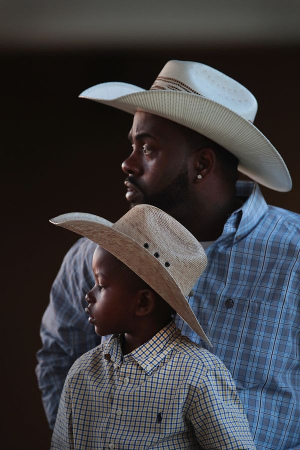 Jamil Hunt shares a saddle with his 6-year-old son Jamil Hunt Jr. as they prepare to ride into the arena for the start of com