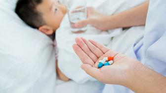 Little boy taking medicine in bedroom