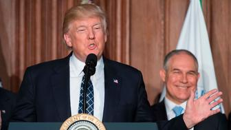US President Donald Trump (C) speaks before signing the Energy Independence Executive Order at the Environmental Protection Agency (EPA) Headquarters in Washington, DC, March 28, 2017, with Vice President Mike Pence (L) and Environmental Protection Agency Administrator Scott Pruitt (R). President Donald Trump claimed an end to the 'war on coal' Tuesday, as he moved to roll back climate protections enacted by predecessor Barack Obama. / AFP PHOTO / JIM WATSON        (Photo credit should read JIM WATSON/AFP/Getty Images)